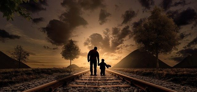 father and son walking on train track