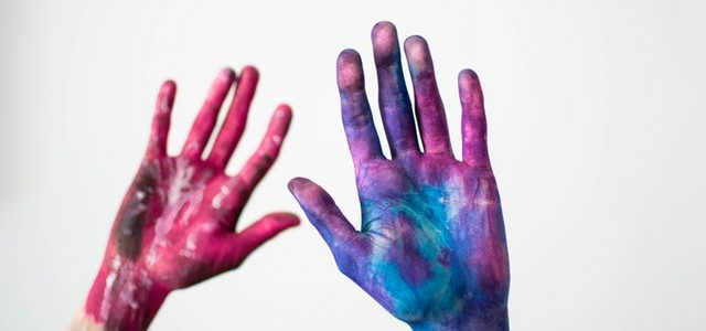 two hands filled with paint against white background