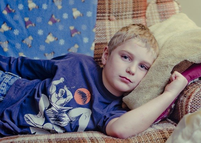 Sick boy laying unhappily on couch