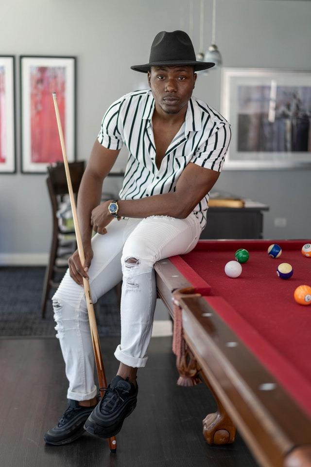 Professional pool player Joe posing on red table