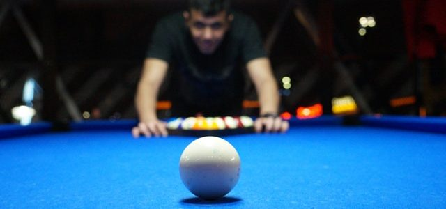 blue pool table with ball and person setting game up